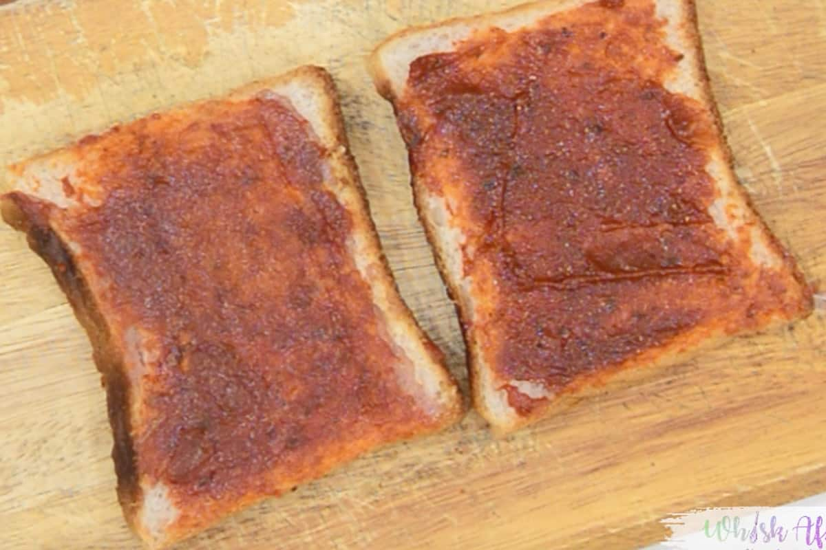 Pizza sauce applied on bread slices.