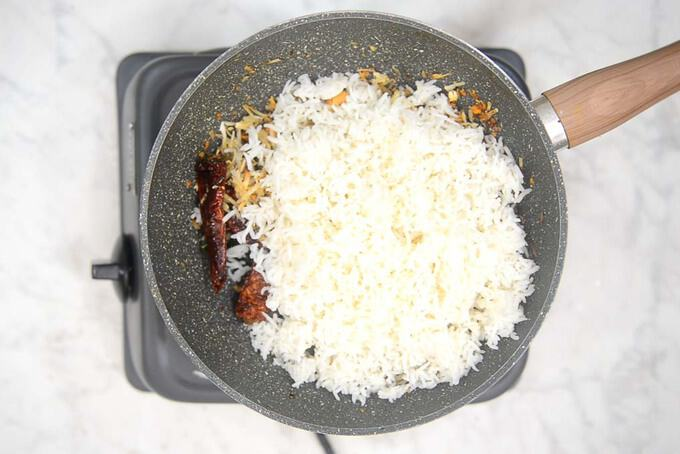 Cooked rice and salt added in the pan.