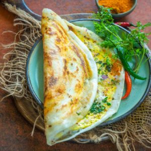 Egg Dosa is a popular South Indian dish where the traditional dosa is topped with eggs and spices. It comes together in just 10 minutes and makes for a great breakfast or snack.
