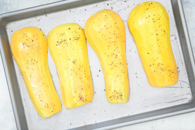 Peeled Butternut Squash Kept on a baking tray and drizzled with oil, salt and pepper.