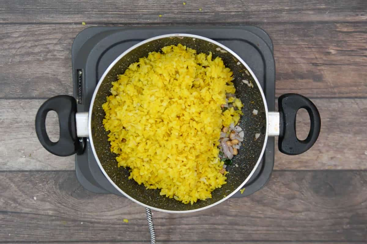 Steamed poha added to the pan.