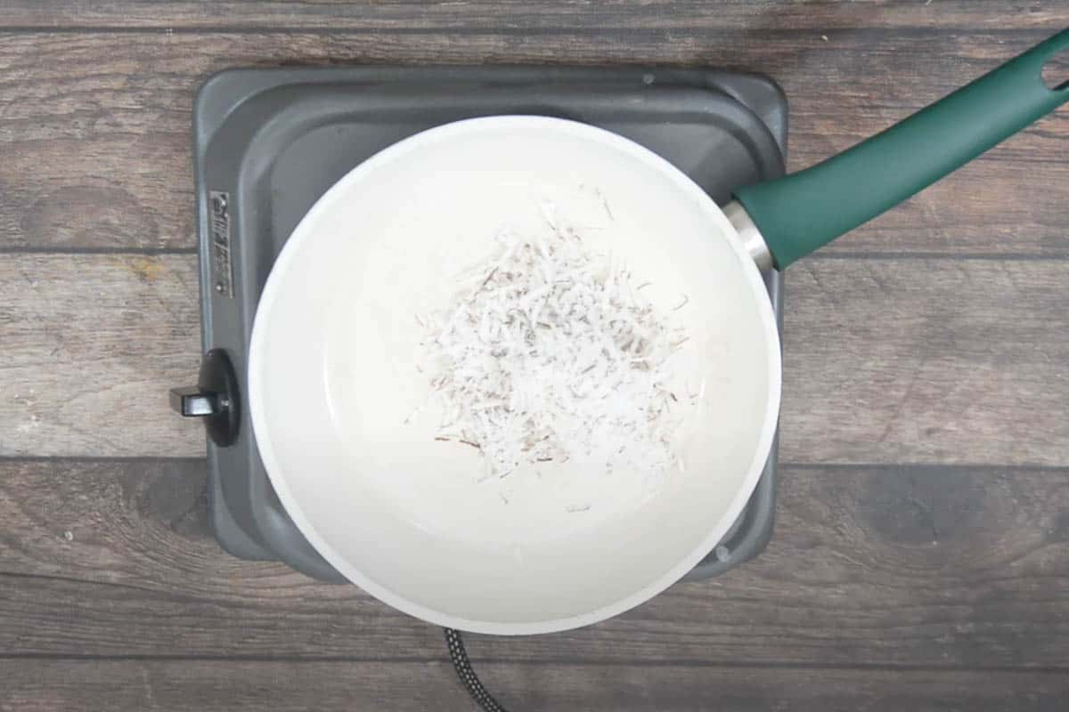 Grated coconut added to a pan.