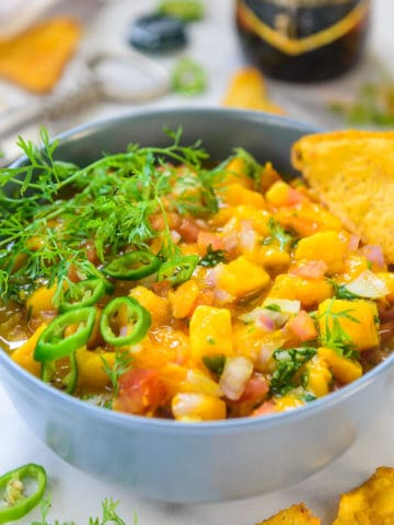 Fresh Mango Salsa is a quick and easy dip that you can whip in just a few minutes to serve along with crackers or chips. This homemade recipe is a family favourite and summer Friday nights are incomplete without it. It is made from fresh mango, red onion, tomato, and lime juice. Do season with salt and pepper for that extra taste. Here is how to make it at home.