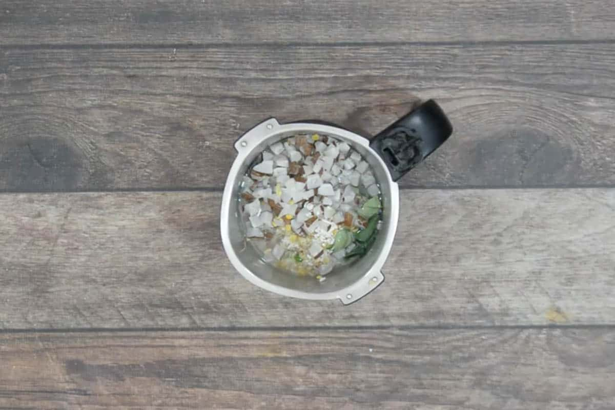 Soaked dal, rice, cumin seeds, ginger, green chilies, curry leaves and coconut added to a grinder.