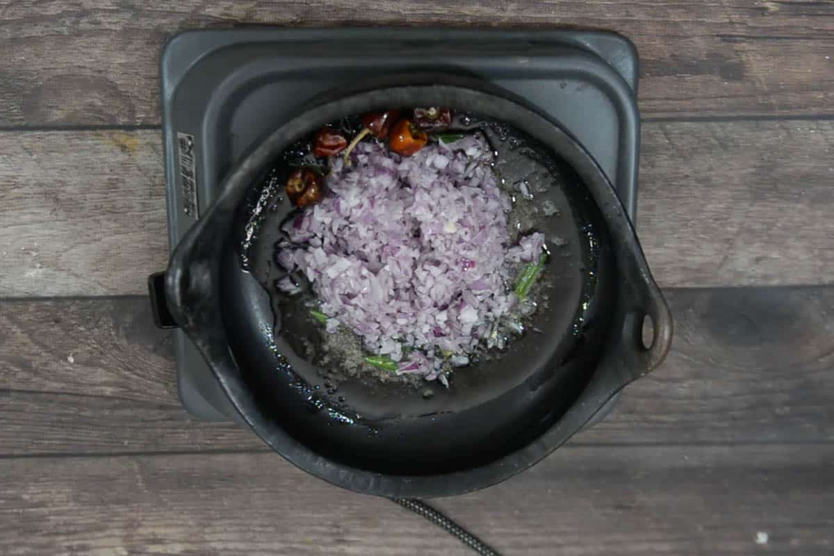 Chopped onion added to the pan.