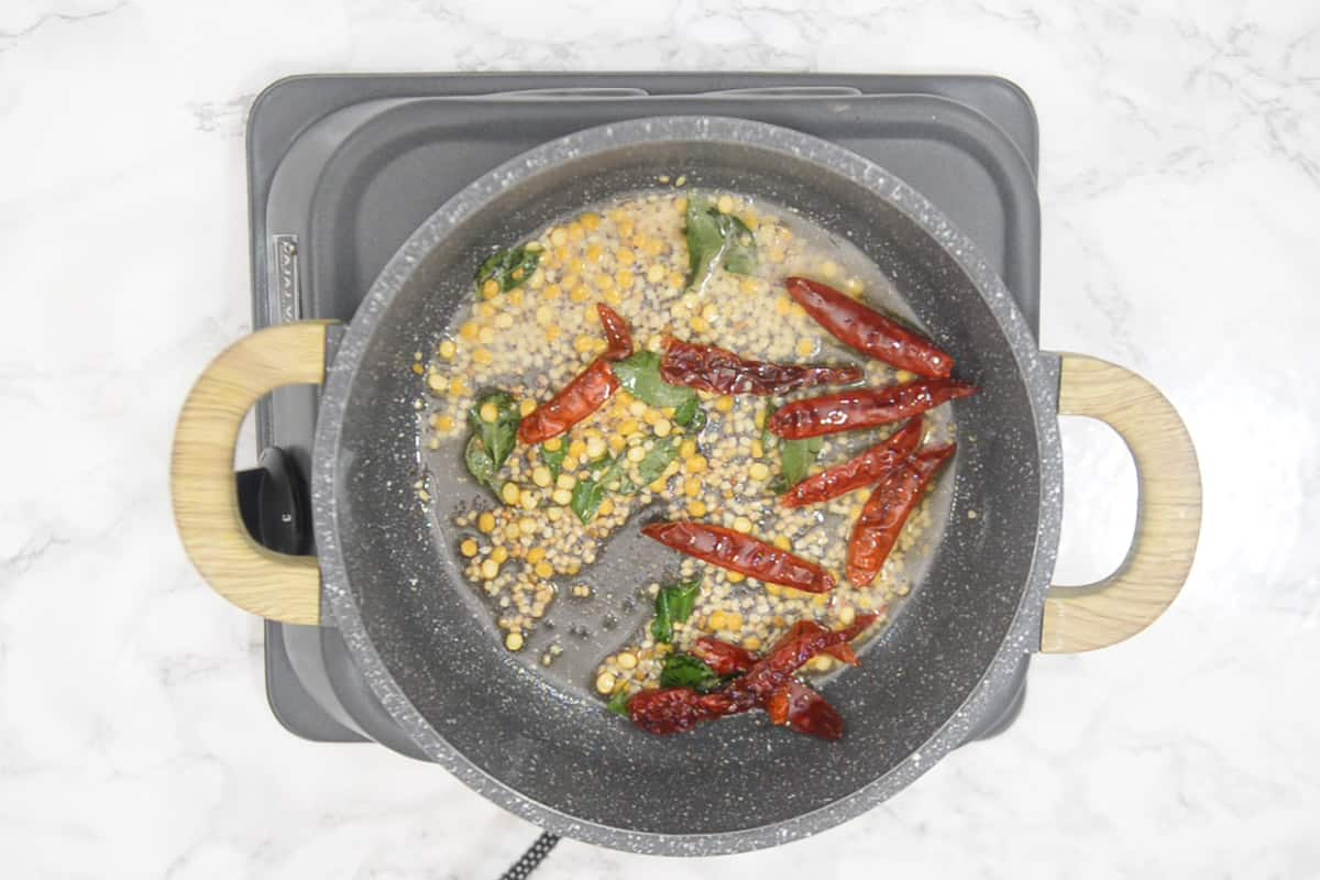 Curry leaves and dry red chillies added in the pan.