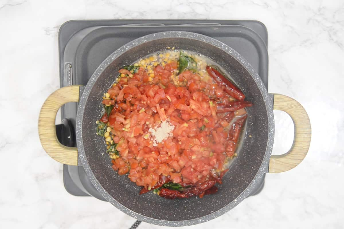Hing and tomato added in the pan.