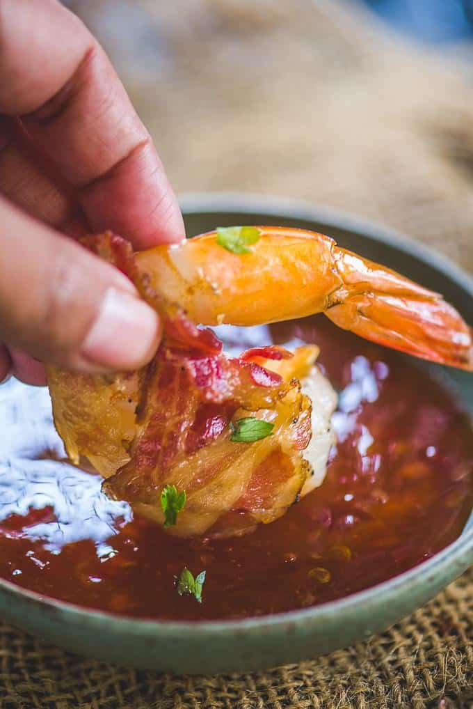 Grilled bacon wrapped shrimp dunked in a dipping sauce.