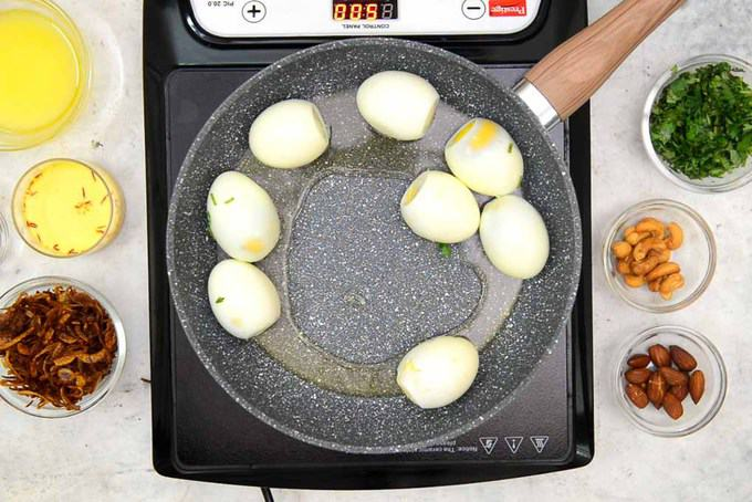 Boiled eggs added in a pan.