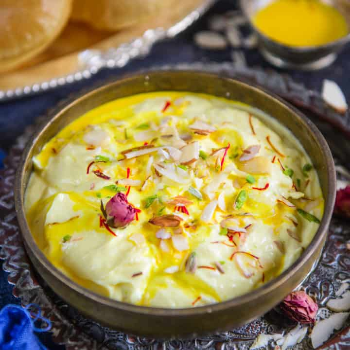 Shrikhand is a sweet dish made using hung curd and powdered sugar and is usually served with puri. It is basically an assortment of silky smooth curd, a hint of flavoring and a crunch of dry fruits. Shrikhand Puri is a delight to eat and a breeze to make. So let's waste no time and see how to make it.