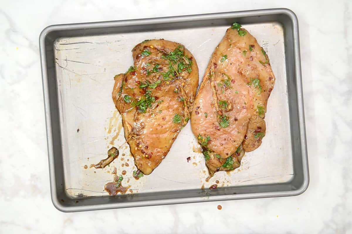 Chicken arranged on a baking tray.