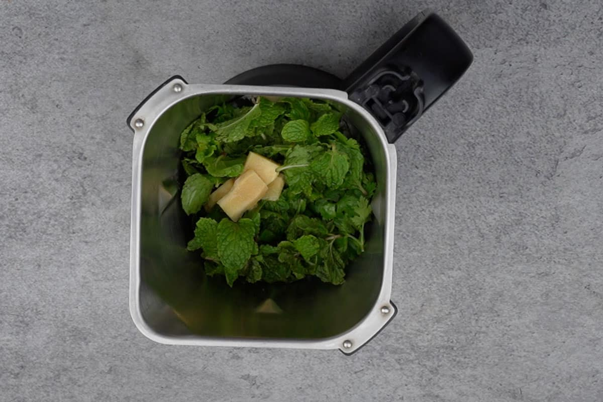 Mint, cilantro and ginger added to a blender.