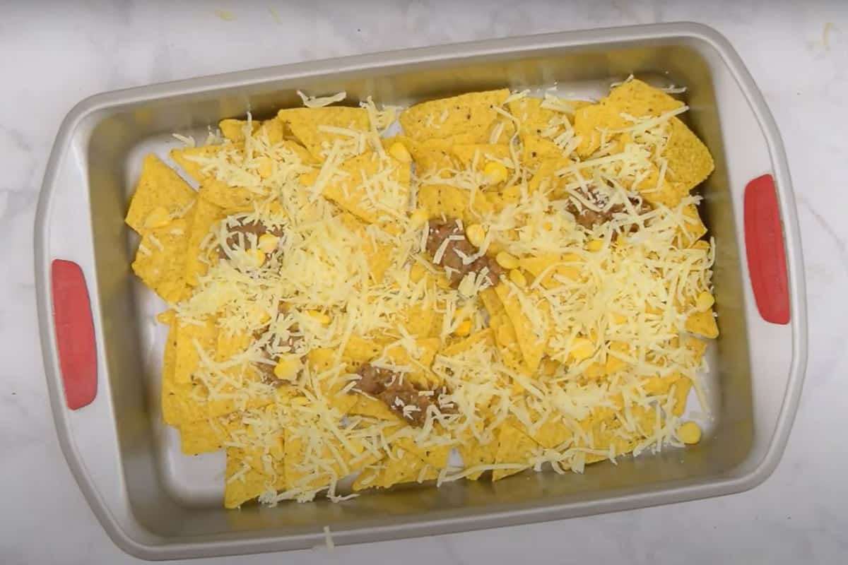 Topped with half of the refried beans, corn kernel, cheddar cheese, and gouda cheese