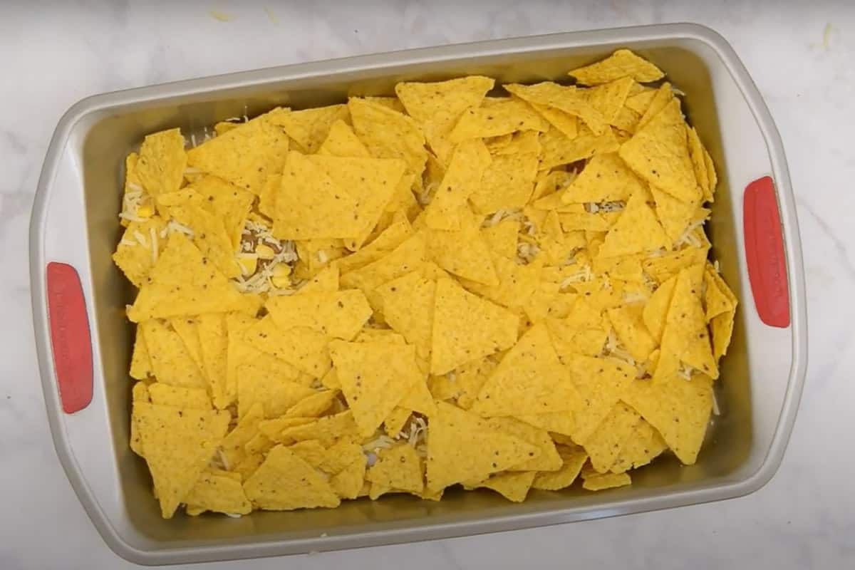 Topped with remaining tortilla chips and beans, corn, and cheese.