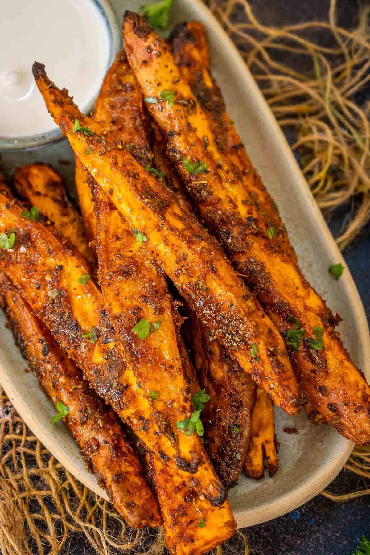 Oven roasted sweet potato wedges served on a plate.