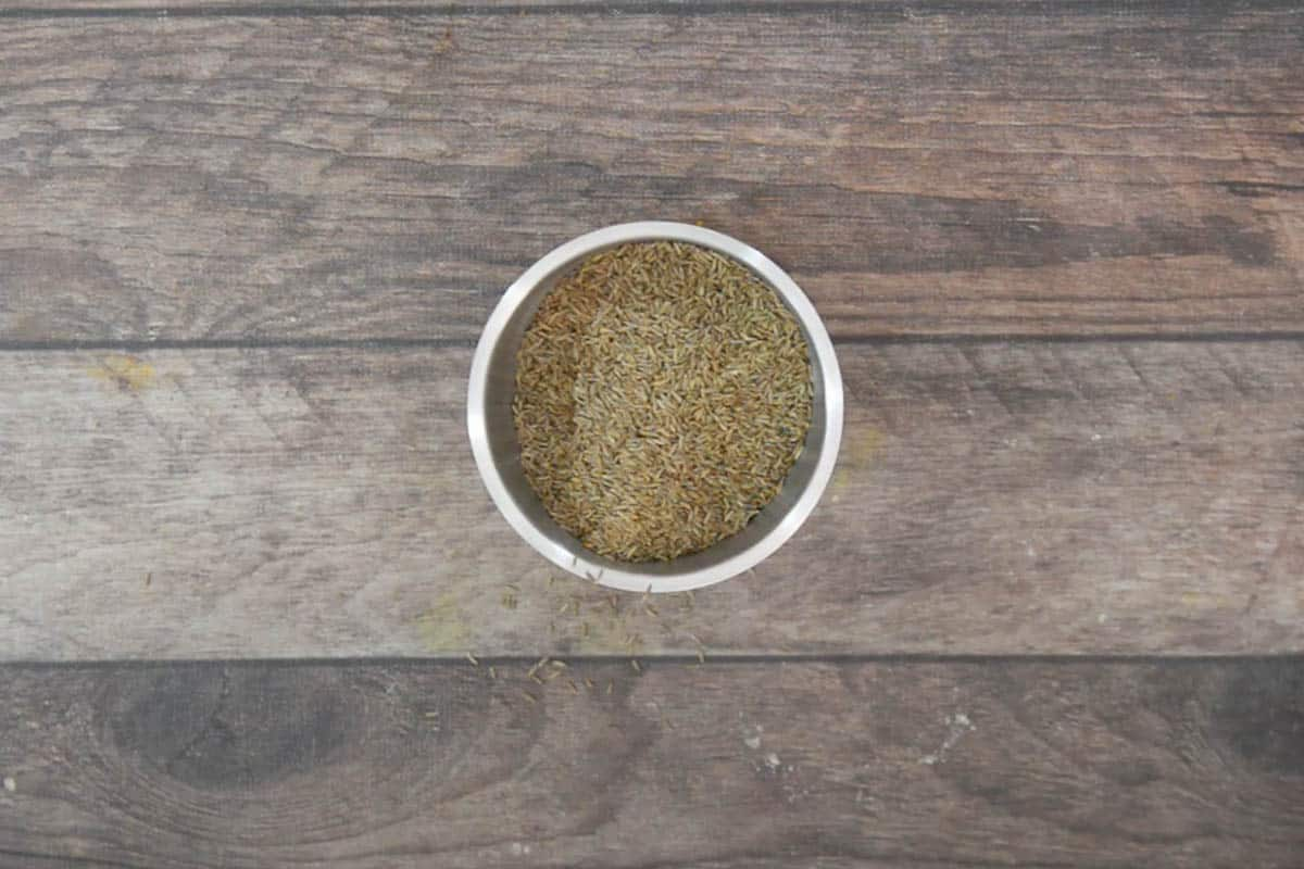 Cooled cumin seeds added to the grinder.