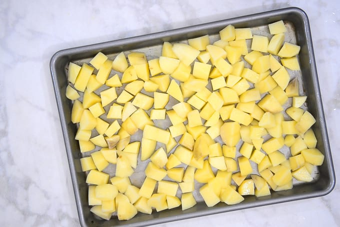 Potatoes lined on a baking tray.