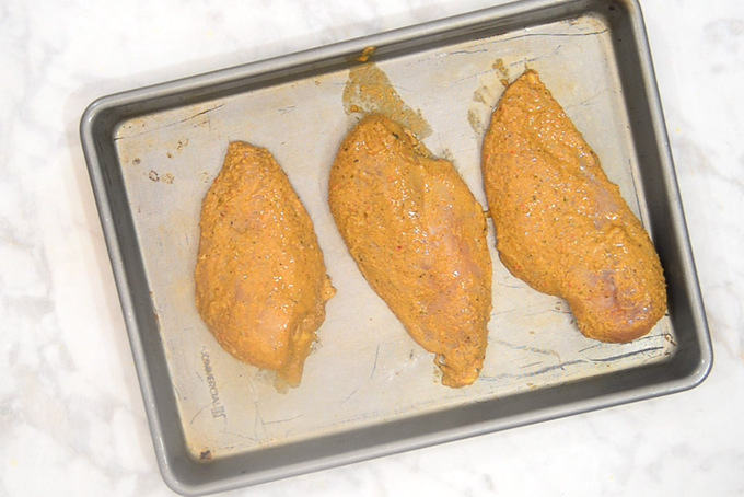 Marinated chicken breast lined on a tray.
