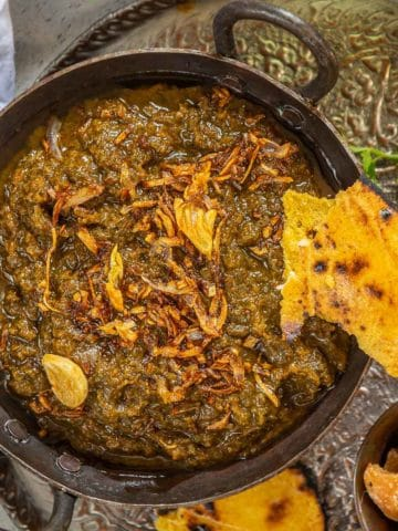 Sarson Ka Saag is a traditional Punjabi dish made with Mustard Greens and other leafy vegetables and a delicious tempering of onion and garlic in ghee. Served with a dollop of White Butter (Makkhan) and crispy warm Makki Ki Roti, this dish is soul-warming.
