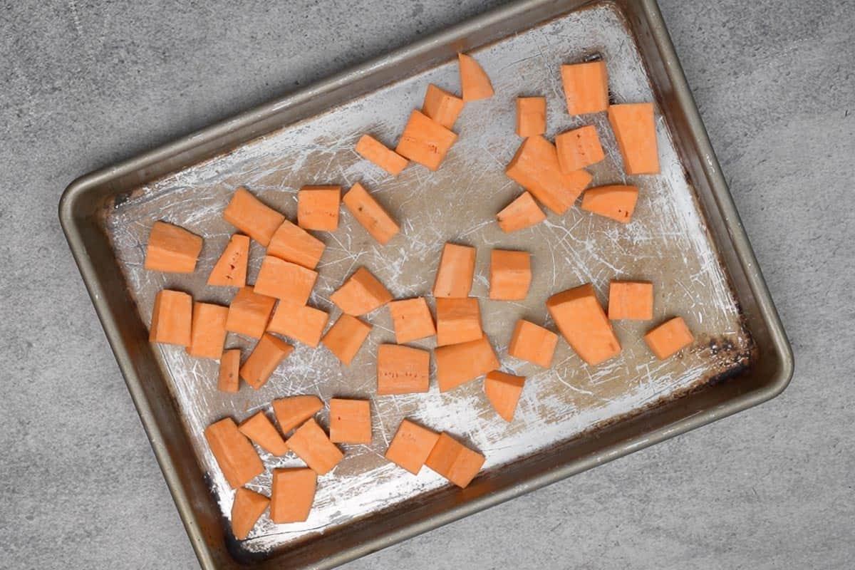 Sweet potato cubes arranged on a baking tray.