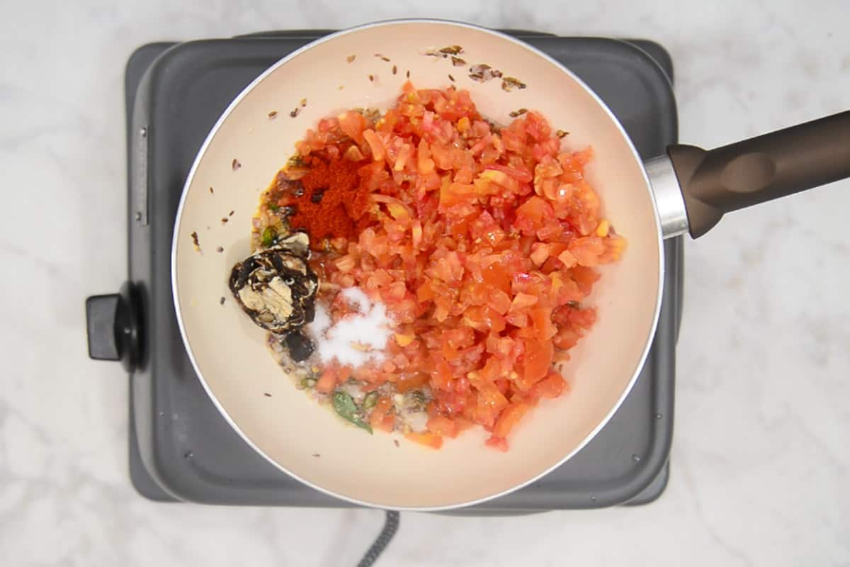 Tomato, red chilli powder, tamarind and salt added in the pan.