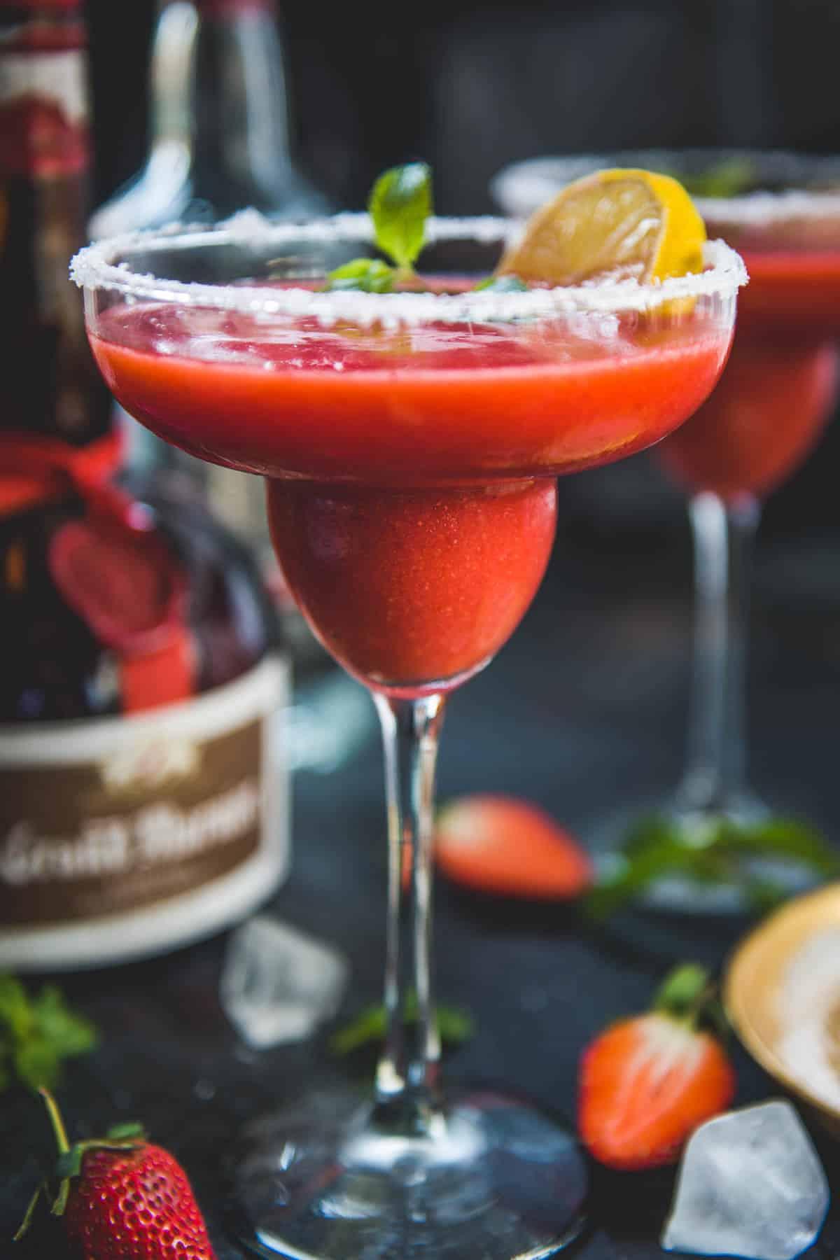 Frozen strawberry margarita served in a margarita glass.
