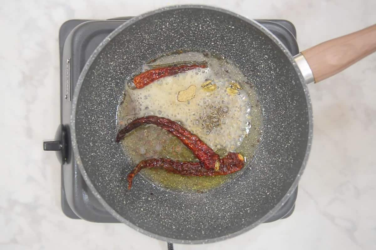 Cardamom, cloves, peppercorns, cinnamon, dry red chillies, cumin seeds and hing added in the pan.