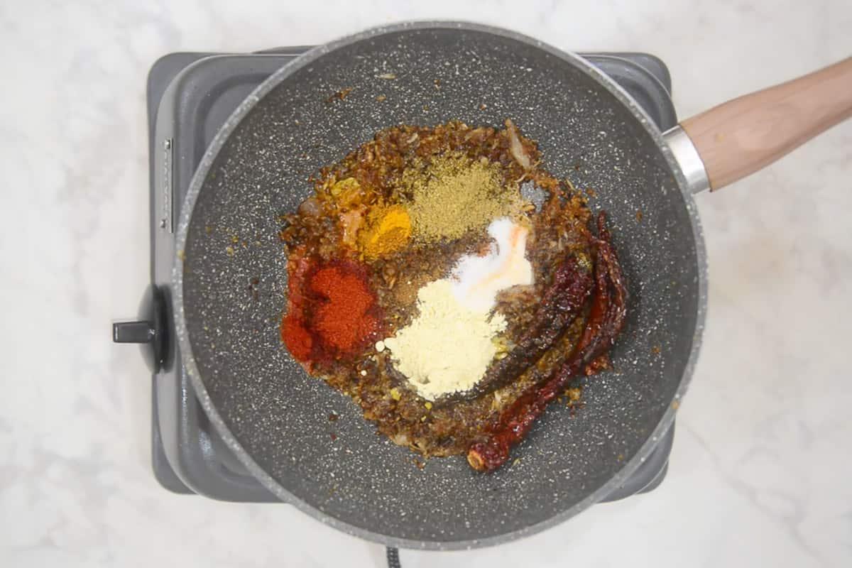 Coriander powder, turmeric powder, red chilli powder, cumin powder, garam masala powder, besan and salt added in the pan.