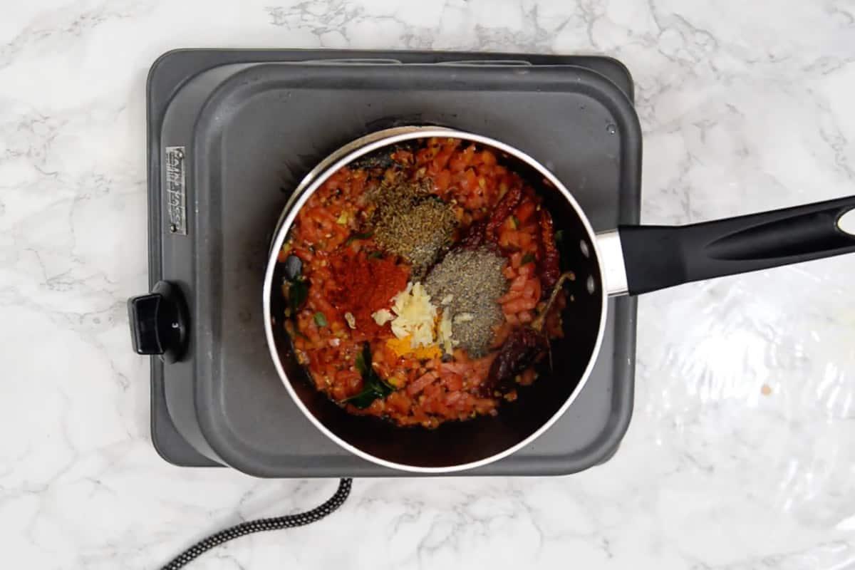 Turmeric powder, red chilli powder, powdered cumin seeds, powdered black peppercorns and garlic added in the pan.