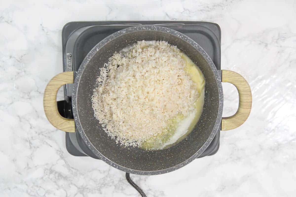 Rinsed rice added in the pan.