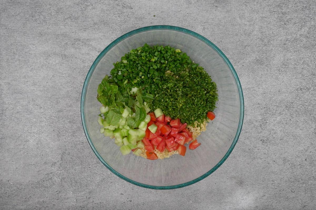Parsley, tomatoes, cucumber and green onions added to the bowl.