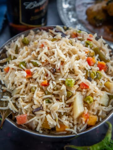 This restaurant-style Veg Pulao is a delicious medley of rice, spices, and vegetables. Also known as Vegetable Pulao Pulav or Indian Pulao, this North Indian dish is very simple and easy to make and pairs perfectly with any raita or curry of your choice.