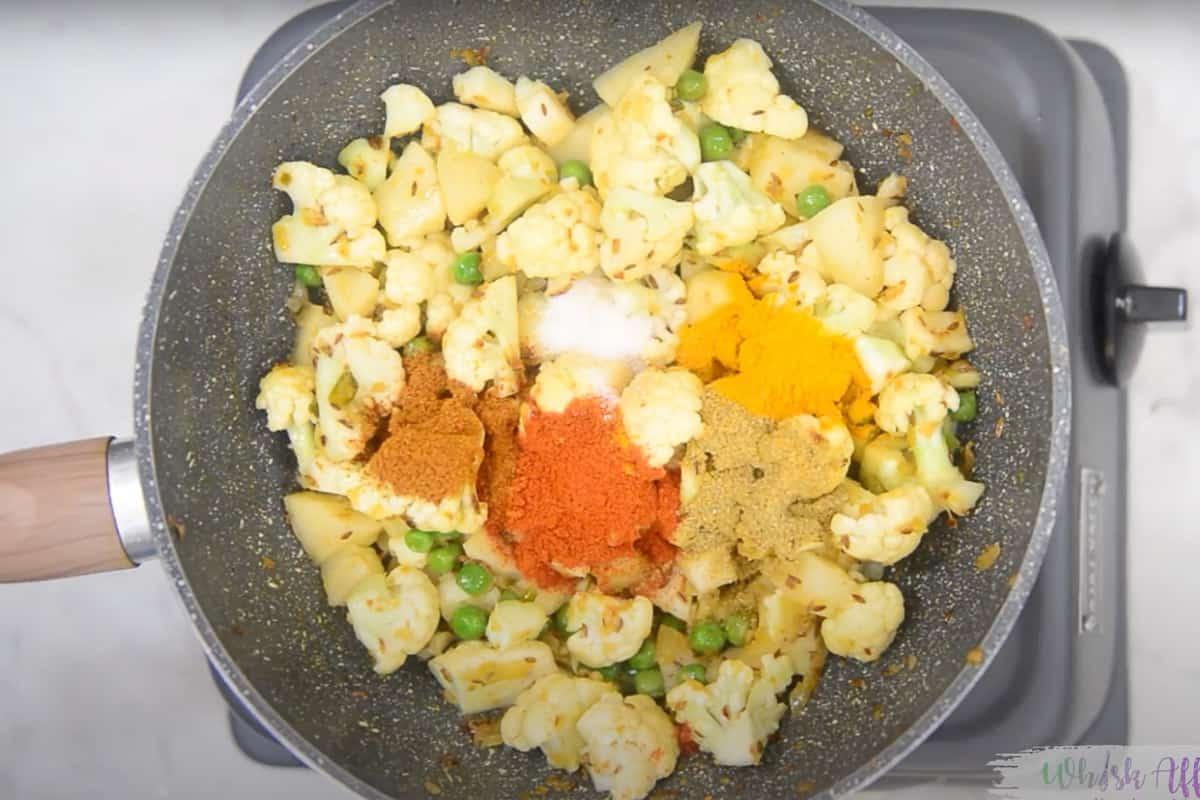 Potato, peas, cauliflower, coriander powder, turmeric powder, red chilli powder, garam masala and salt added in the pan.