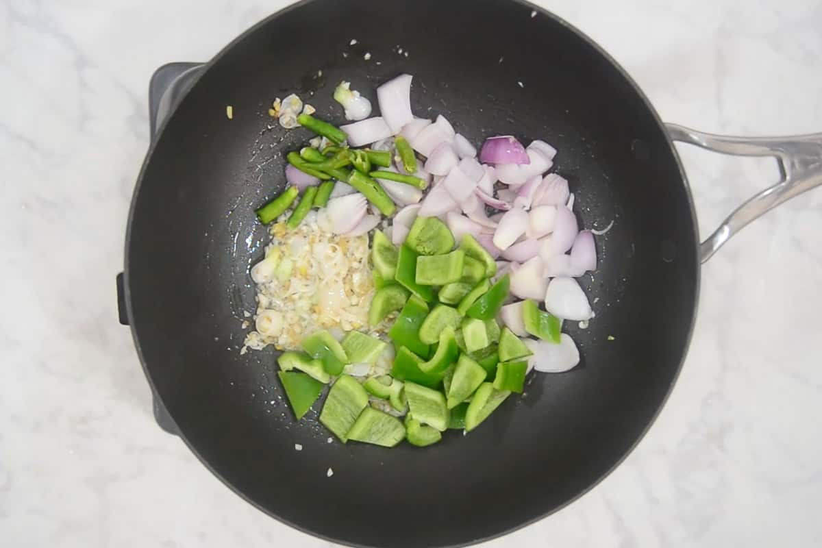 Onion, green chilli and capsicum added in the wok.
