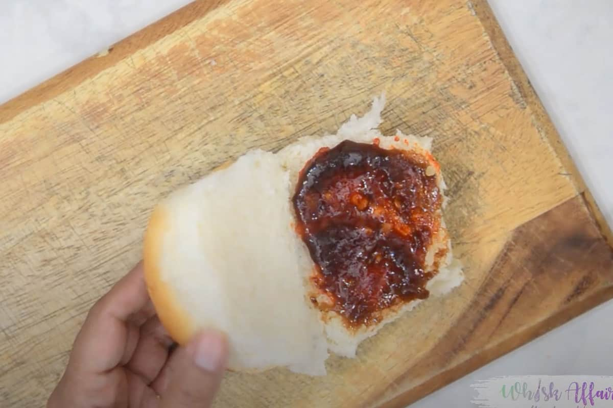Pav slathered with garlic chutney and tamarind chutney.