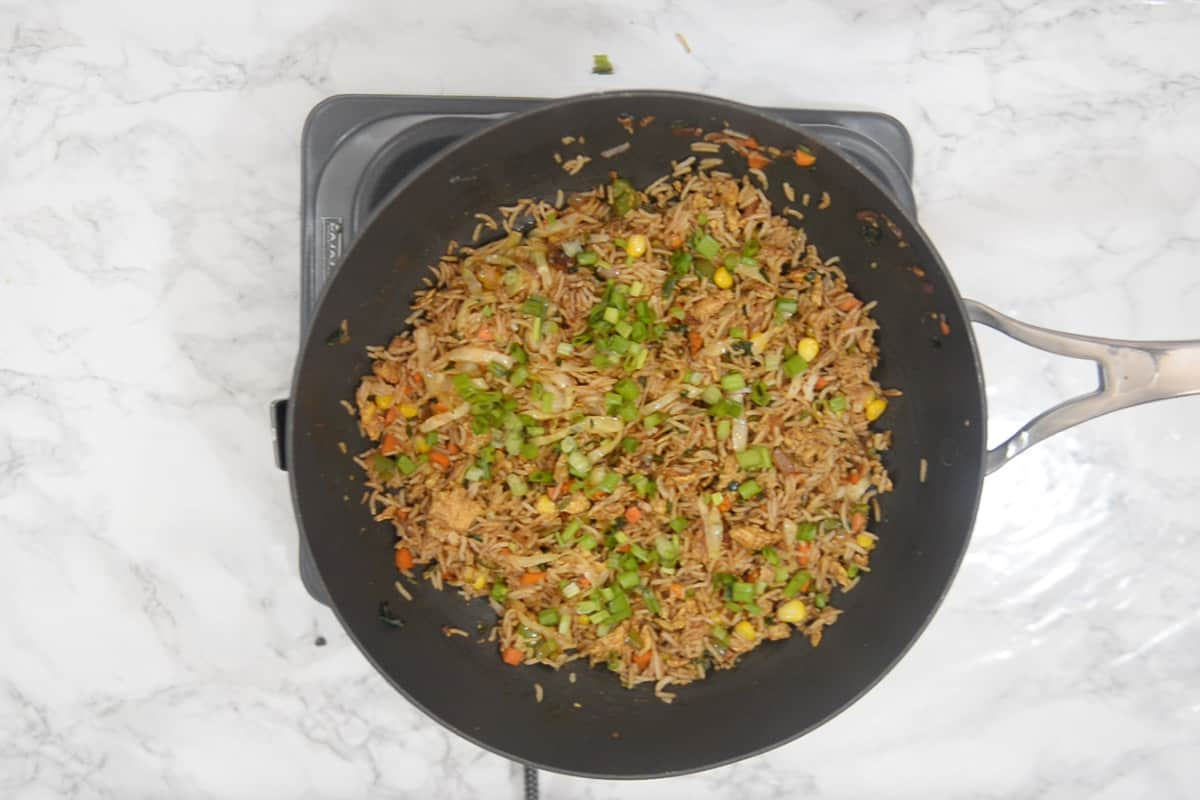 Ready egg fried rice garnished with spring onions.