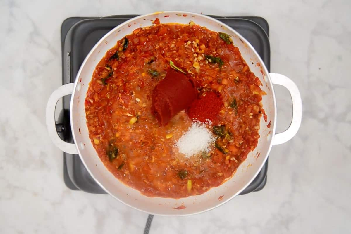 Tomato paste, red chilli powder and sugar added in the pan.