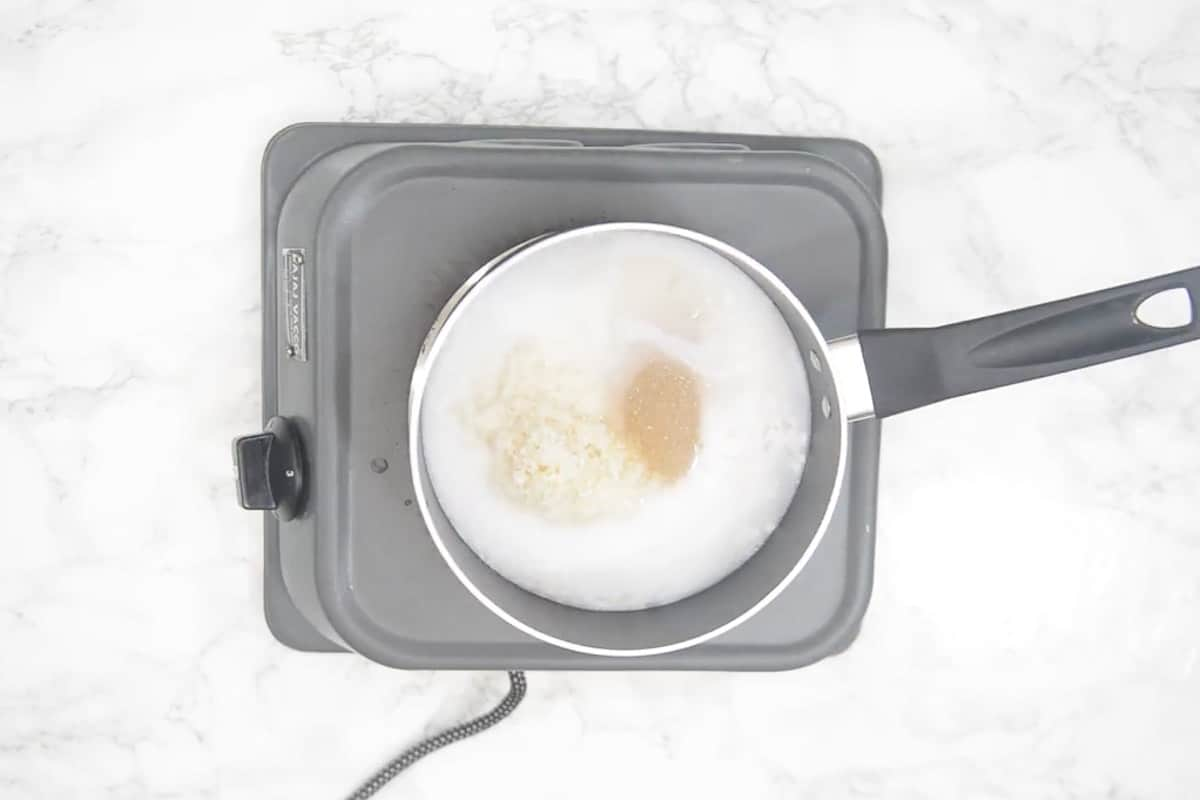 Rice added in a pan along with water, coconut milk, salt and sugar.