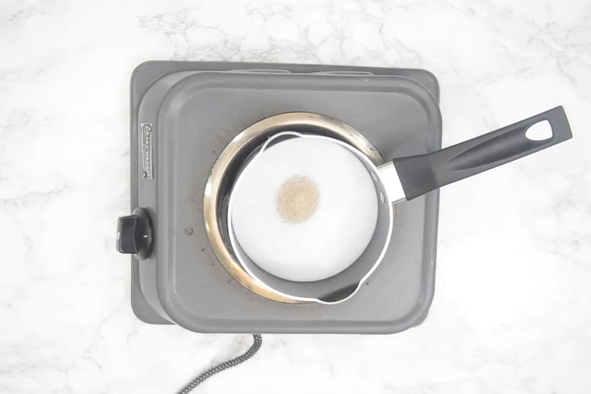Coconut milk and sugar added in a pan.