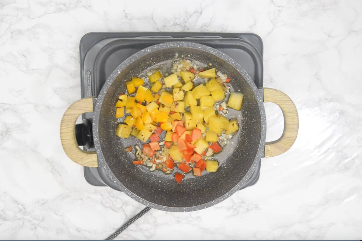 Pineapple and bell peppers added in the pan.