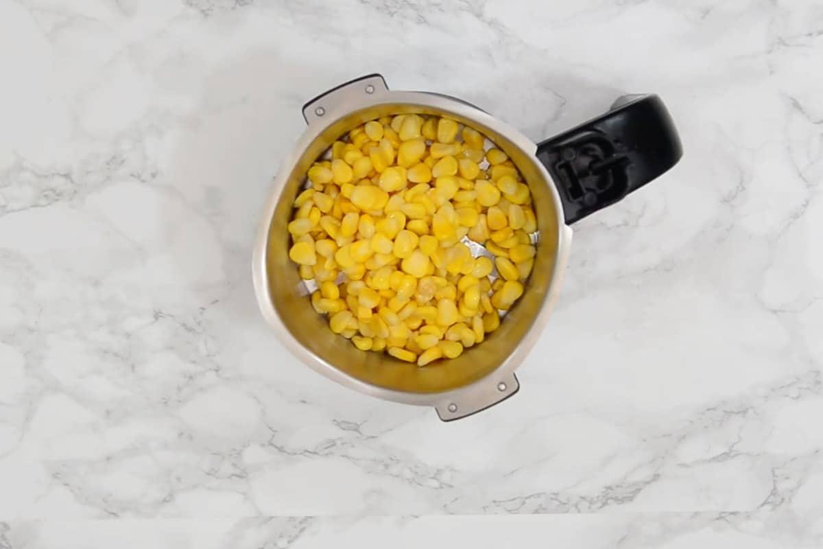 Corn kernels added in a grinder.