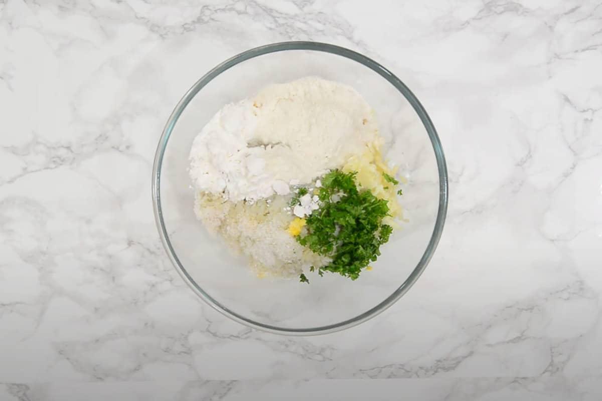 Corn, potatoes, cheese, corn flour, all purpose flour, salt, sugar, green chilli, coriander and baking powder added in a bowl.
