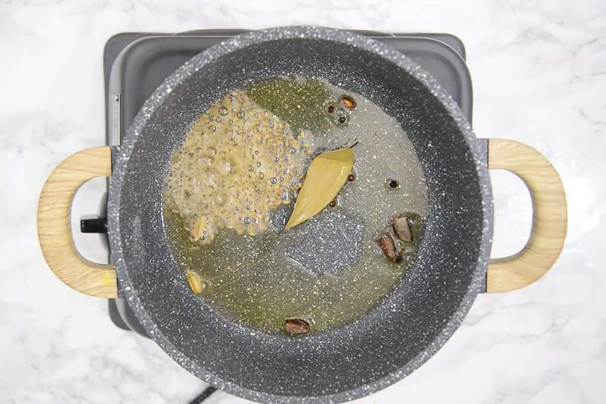 Cumin seeds, bay leaf, black pepper, cinnamon, green cardamom and black cardamom added in the pan.