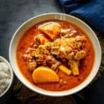 Made especially for the elite class travelling in First Class compartments of Indian railways during pre independence time, Railway Mutton Curry is a milder take on the spicy Indian Mutton Curry. Here is how to make Railways Mutton Curry Recipe.
