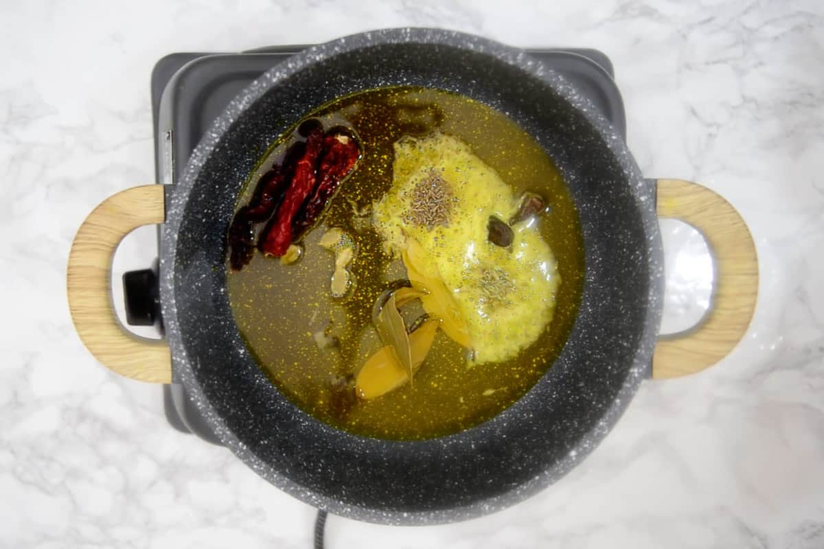 Bay leaves, cloves, green cardamom, black cardamom, fennel seeds, cumin seeds and dry red chillies added in the pan.