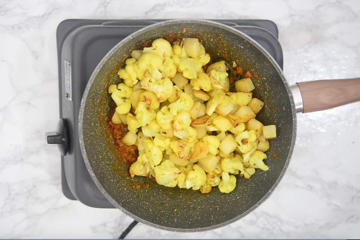 Fried cauliflower and potatoes added in the pan.