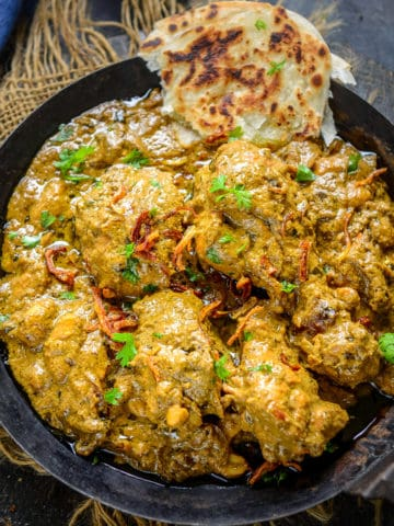 Coriander Chicken Curry is a green chicken curry made using chicken pieces, fresh coriander, mint, dry fruits, and a few spices. It pairs well with Indian bread or rice. Here is how to make it.