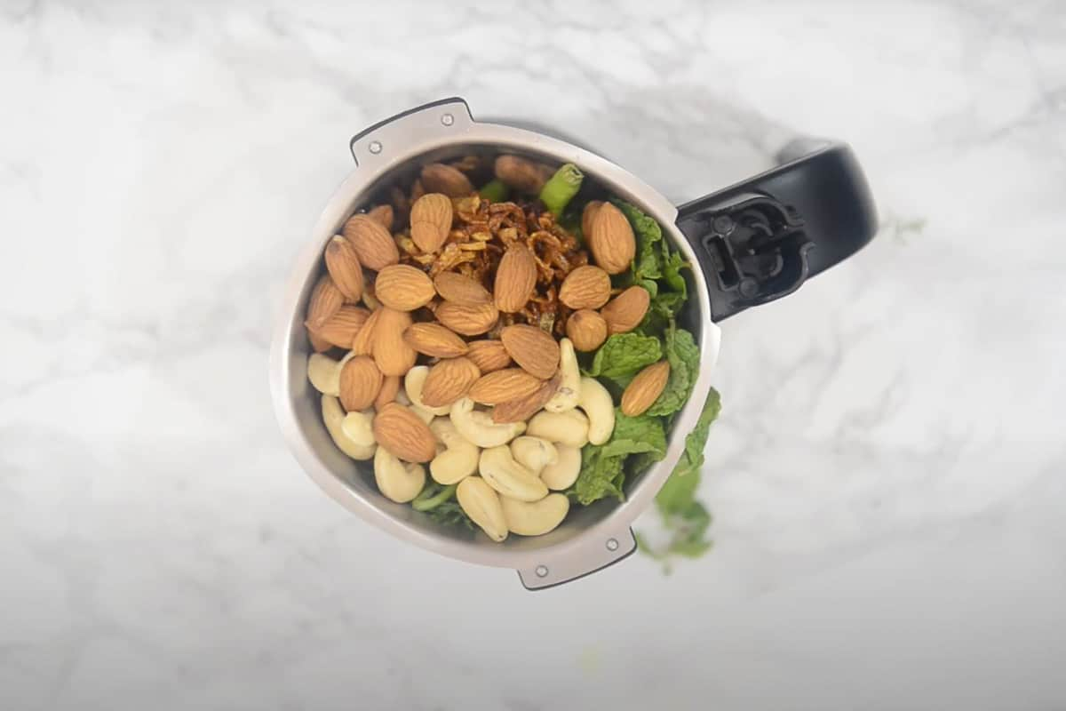 Coriander, mint, green chili, fried onion, cashew nuts, almonds added in a grinder.