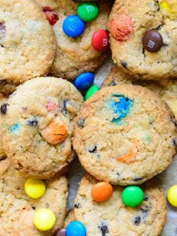 Loaded with chocolate chips and M&M, these crispy Eggless M&M Cookies are a breeze to make at home. Make these eggless cookies this Christmas from scratch for a festive treat. Here is how to make it.