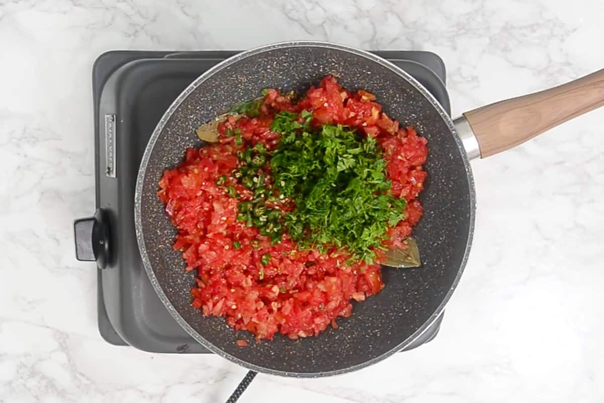 Tomato, fresh coriander and green chilies added in the pan.